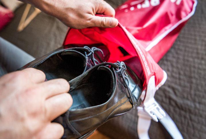 Benjamin David packt in seiner Wohnung Schuhe in eine wasserdichte Tasche