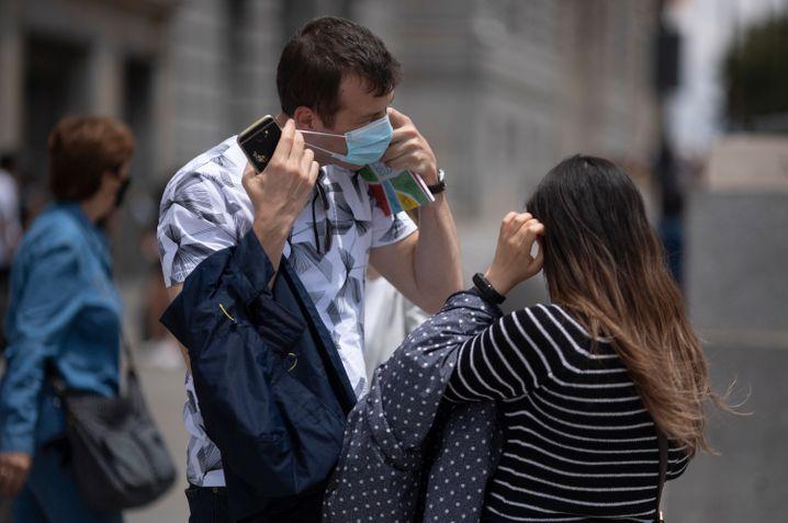 Ein Mann nimmt an der Puerta del Sol seine Maske ab