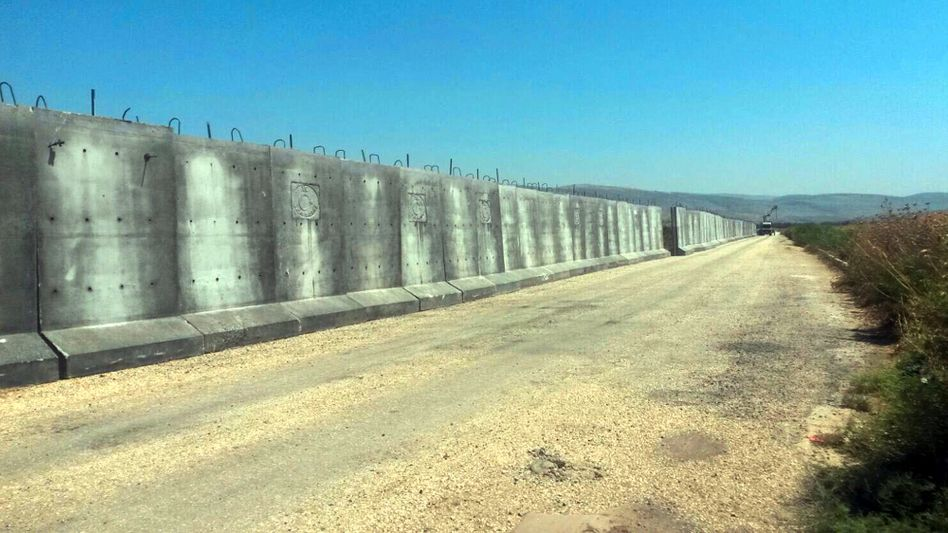 The construction of a security wall along the border between Turkey and Syria: Increased controls mean that many trying to escape Assad's barrel bombs are unable to get out of the country.