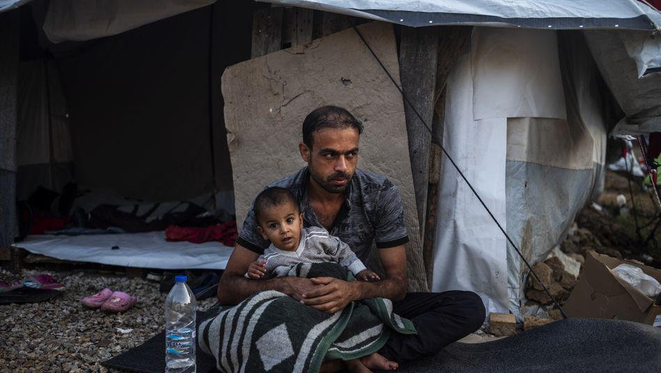Ein Mann sitzt mit einem Kind vor einer Unterkunft im Flüchtlingslager Moria auf der griechischen Insel Lesbos