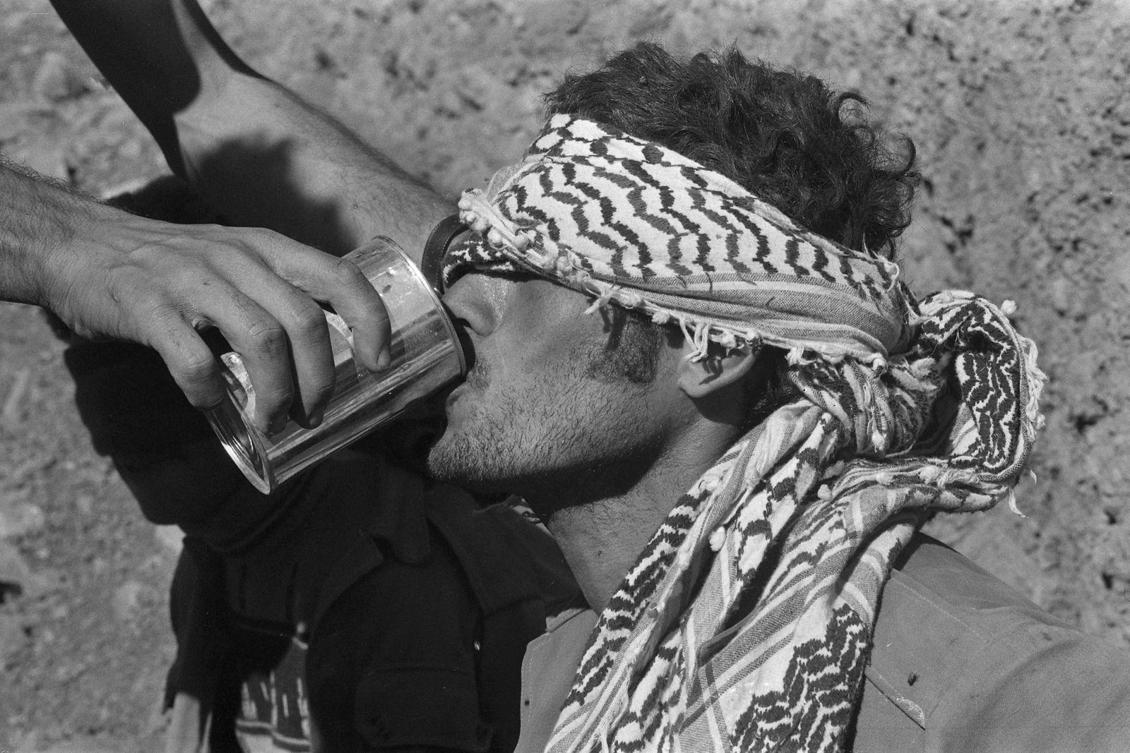 Syrischer Gefangener, Soldat der syrischen Armee, gefesselt mit verbundenen Augen, bekommt Wasser zu trinken, waehrend d