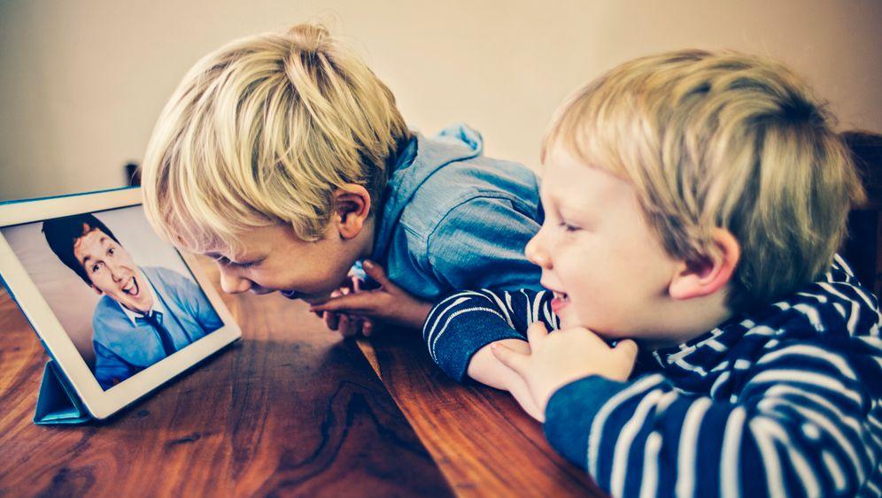 Jungs vor einem Foto ihres Vaters: Erfahrungen teilen statt Dinge bereden