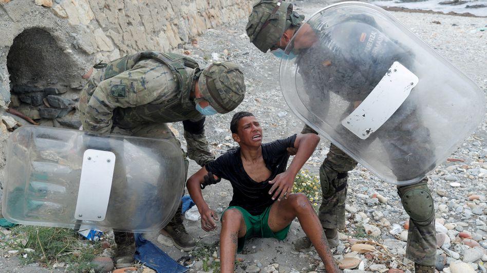 Spanische Sicherheitskräfte und ein Jugendlicher am Strand von Ceuta: Der Minderjährige ist mithilfe von Plastikflaschen in die Exklave geschwommen