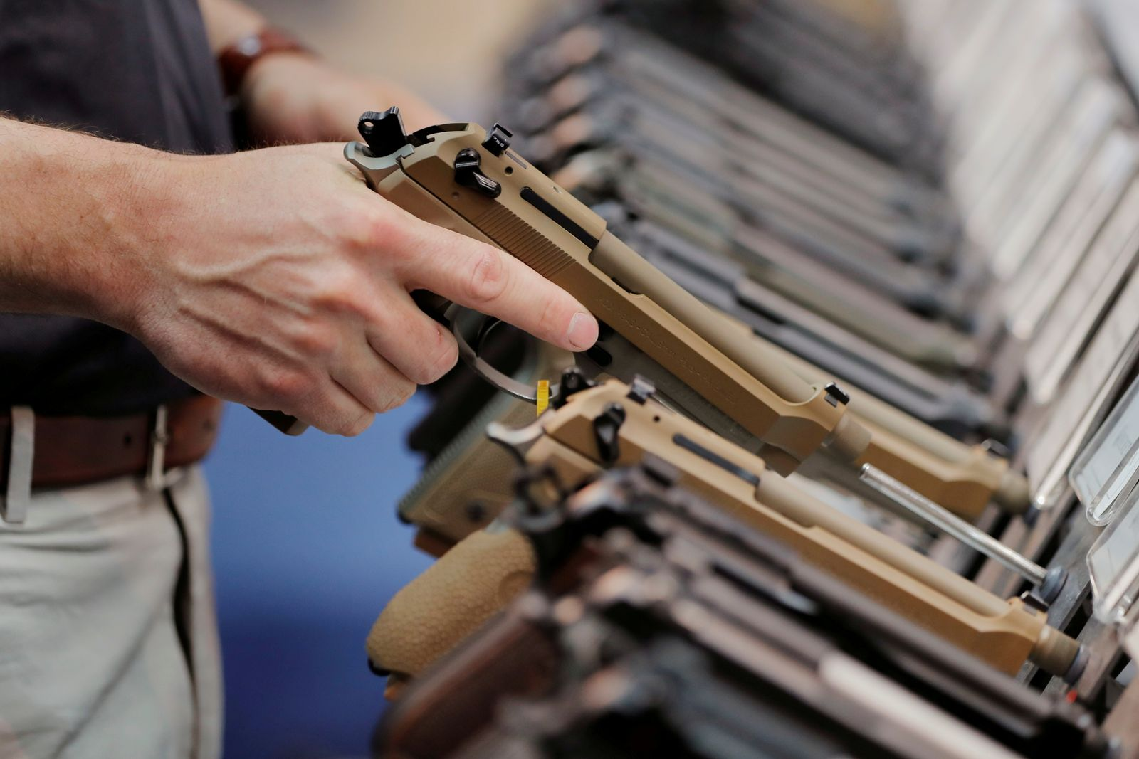 FILE PHOTO: A man inspects a handgun inside of the Beretta booth during the National Rifle Association (NRA) annual meeting in Indianapolis, Indiana