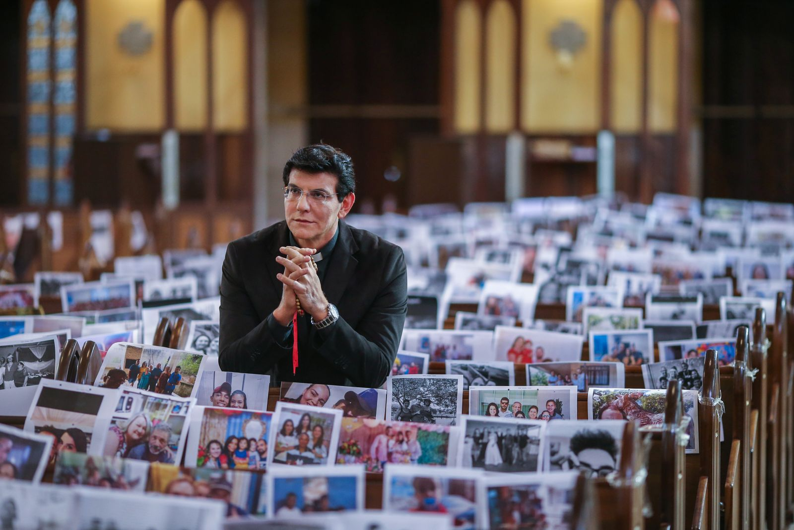 Catholic priest Manzotti prays before a mass with photos of the faithful over the church's banks during the coronavirus disease (COVID-19) outbreak in Curitiba
