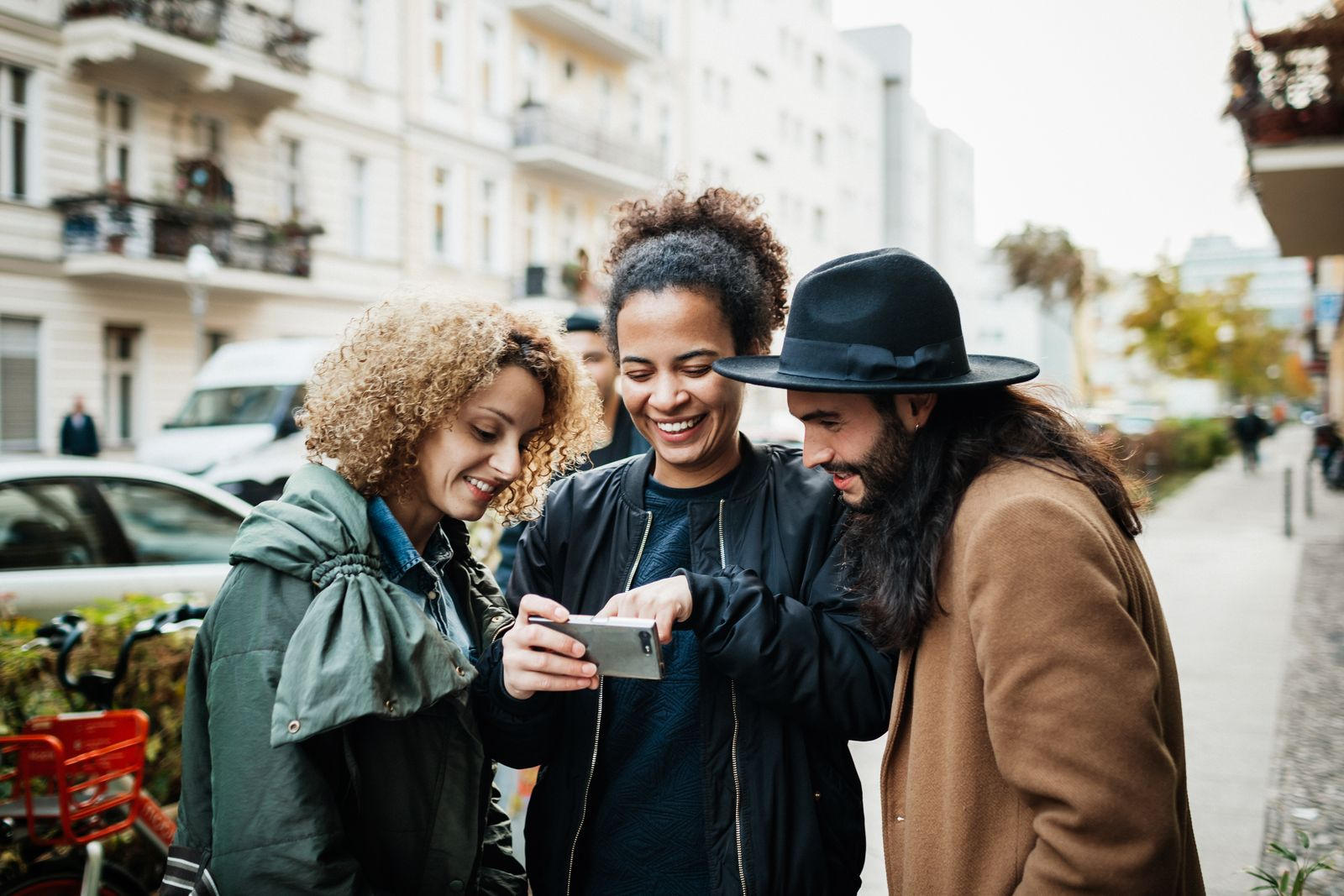 Group Of Friends Looking At Smartphone In Street