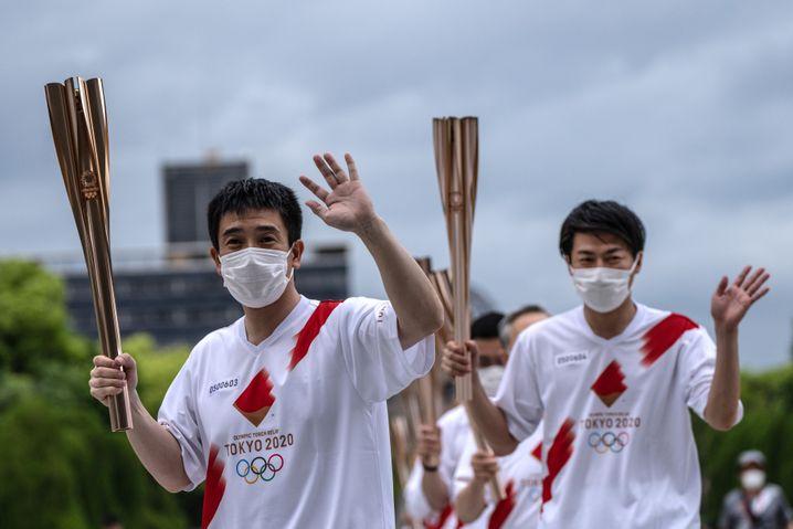 Fackelträger mit Schutzmaske: Die Olympischen Sommerspiele in Tokio stehen wegen des Infektionsrisikos in der Kritik