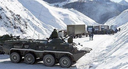 A Russian armoured personnel carrier watches trucks loaded with mandarines at the Russian-Georgian checkpoint of Nizhnyi Zaramag in North Ossetia. During the communist era, Abkhazia was a bountiful source of fruit for the Soviet Union and produced around 120,000 tons of citrus a year.