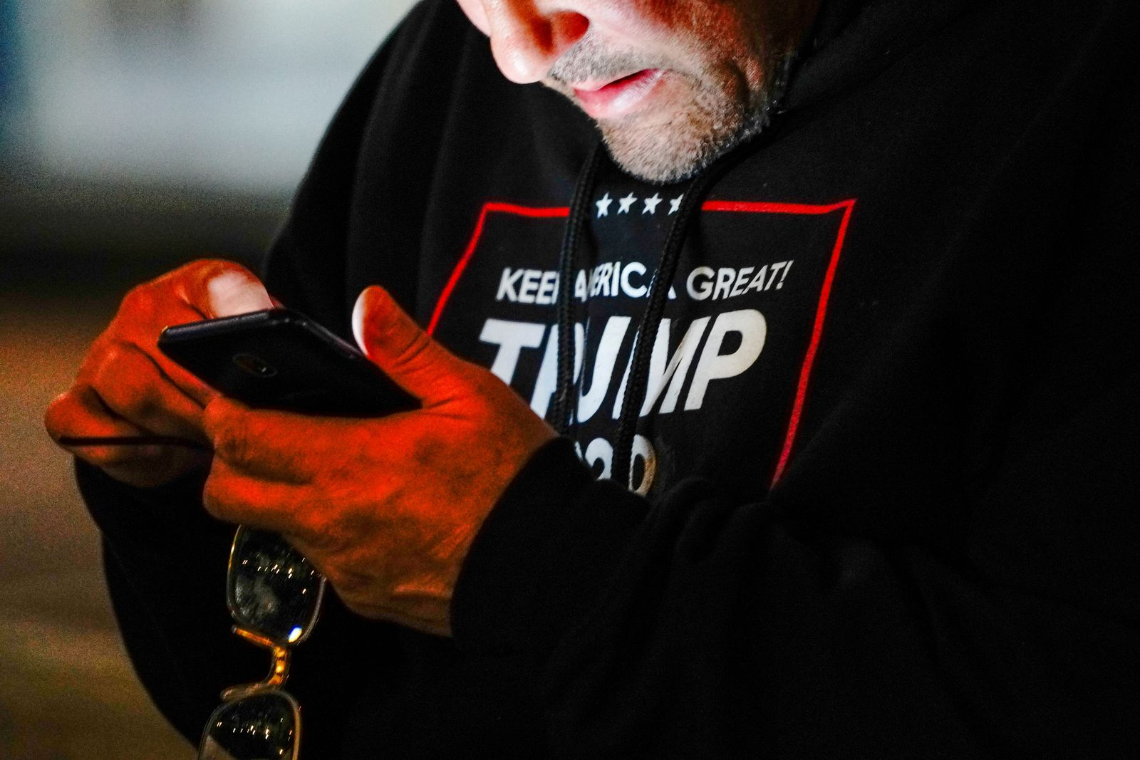 "FILE PHOTO: A man wearing a ""Trump 2020"" sweatshirt uses his mobile phone during a ""Stop the Steal"" protest outside Milwaukee Central Count the day after Milwaukee County finished counting absentee ballots, in Milwaukee"