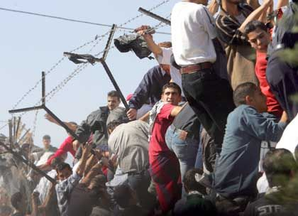 Chaos in der Mukata: Anhänger Arafats klettern über eine Mauer auf das Gelände des Amtssitzes