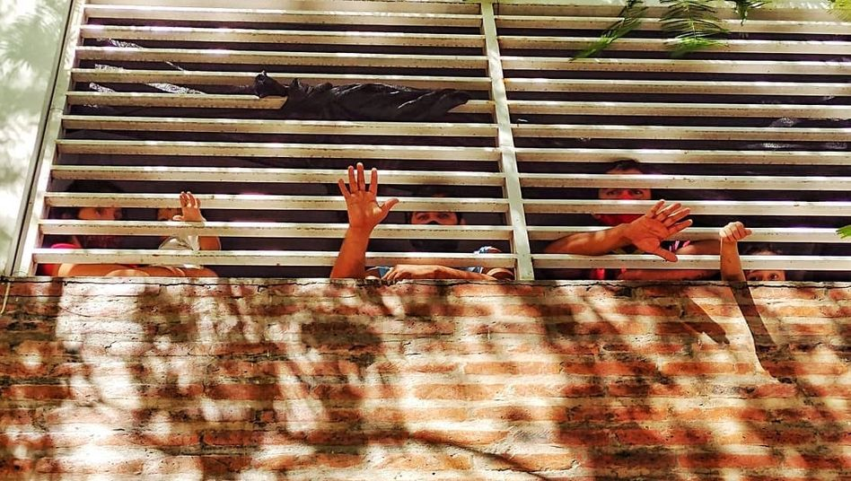 People sticking their hands through the barred window of an isolation center in the Argentinian province of Formosa
