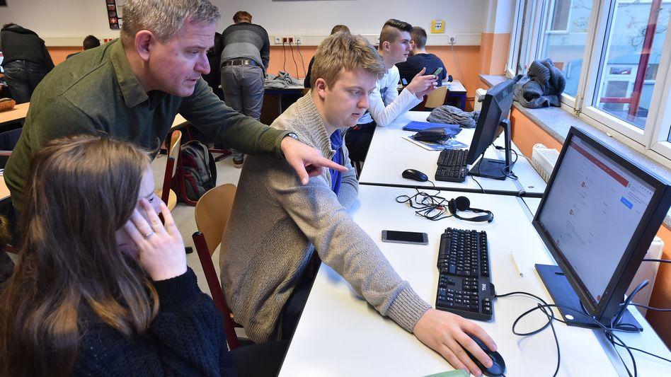 Ein Lehrer erklärt Schülern eine Aufgabenstellung auf einem Computer