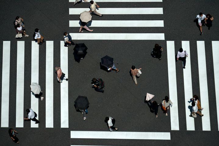 Passanten mit Sonnenschirmen in Tokio