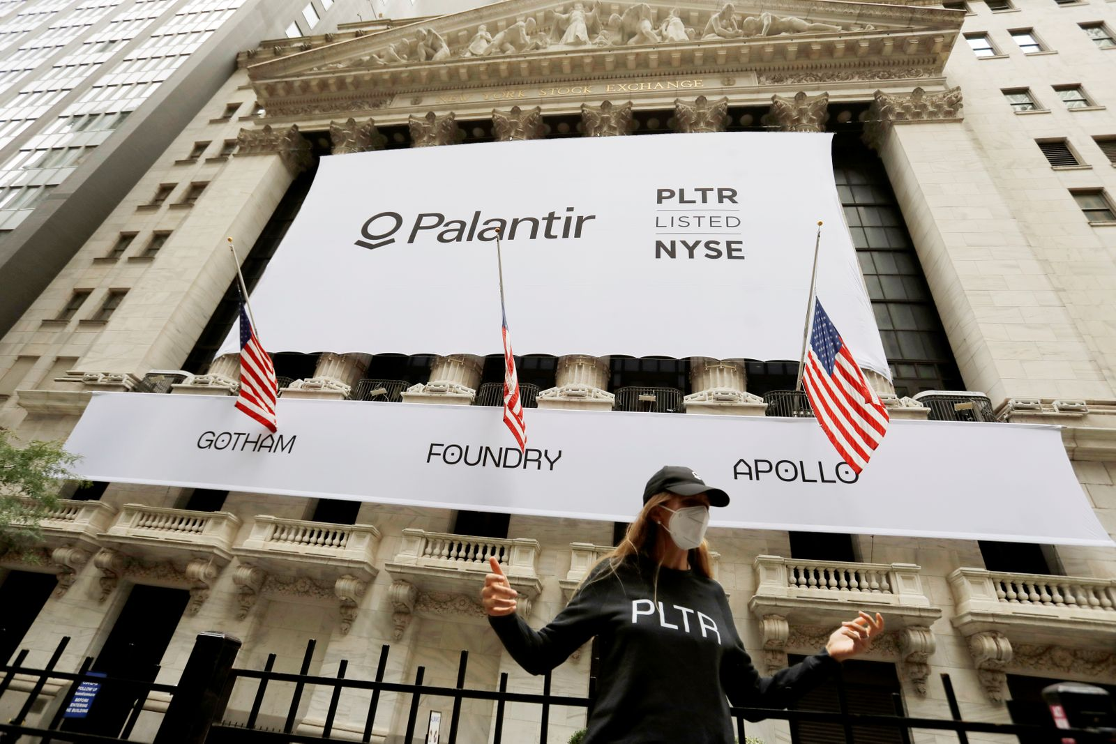 A person poses in front of a banner featuring the logo of Palantir Technologies (PLTR) at the New York Stock Exchange (NYSE) on the day of their initial public offering (IPO) in Manhattan, New York City