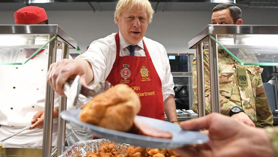 Boris Johnson am 21. Dezember bei einem Truppenbesuch in Estland und der Essenausgabe für die Soldaten