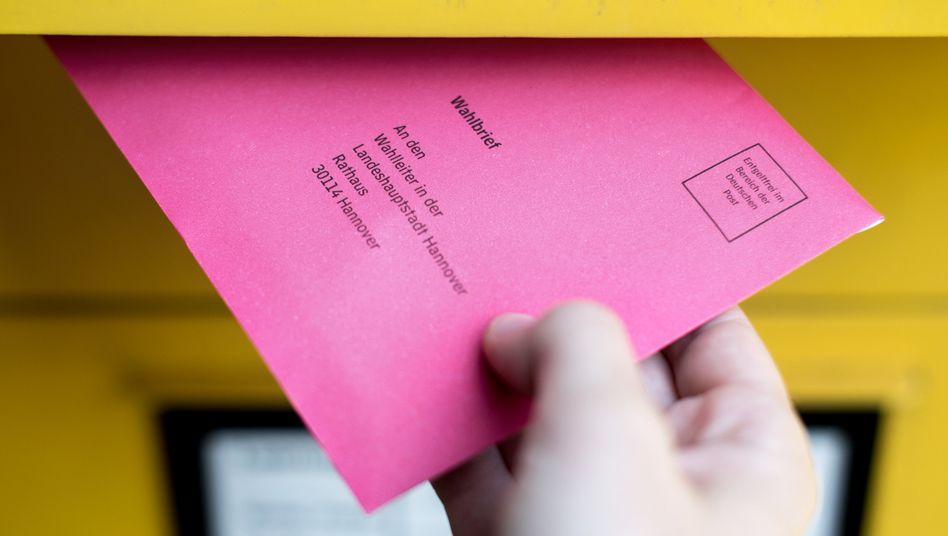 Eine Frau steckt ihren Wahlbrief für die Bundestagswahl 2017 in einen Postkasten (Archivbild)