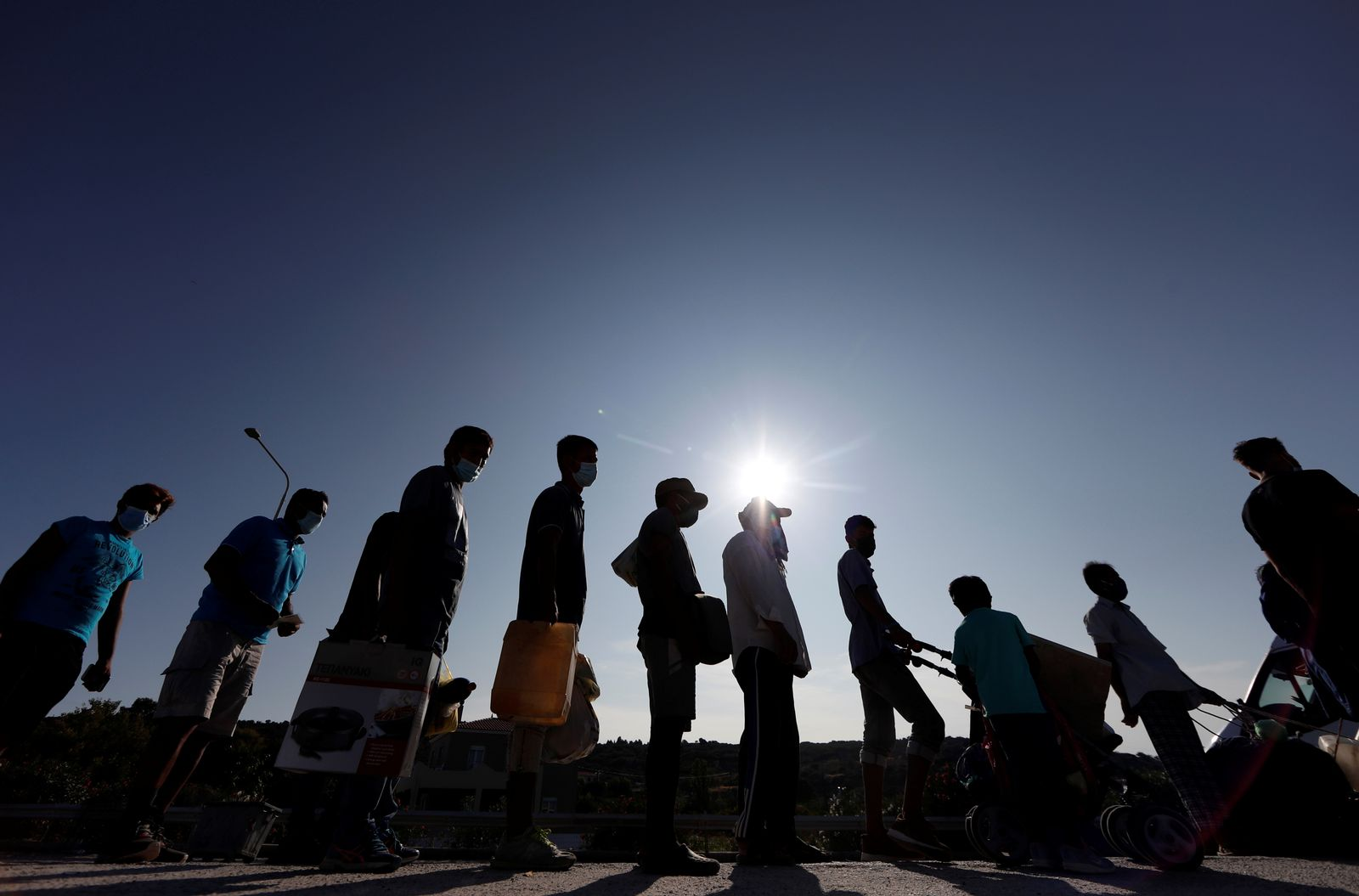 Refugees and migrants from the destroyed Moria camp line up to enter a new temporary camp, on the island of Lesbos