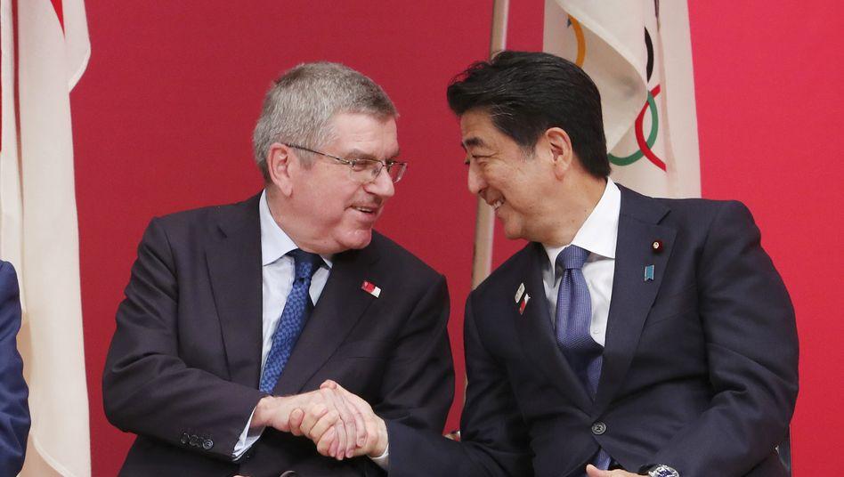 """Thomas Bach (l.) und Shinzo Abe: Die olympische Flamme werde in Japan verbleiben und """"könnte das Licht am Ende des Tunnels sein"""""""