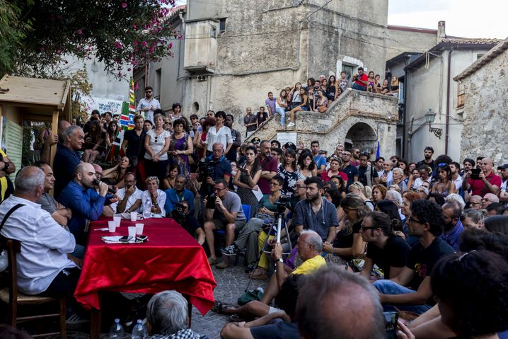 """Roberto Saviano (third from left, with microphone), writer and journalist, during an event together with Mimmo Lucano, the mayor of Riace (second from left). When it comes to the Salvini/Di Maio government, Saviano says, """"There are only accomplices or rebels."""""""