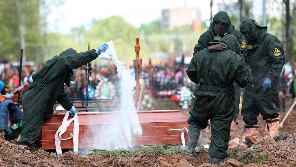 Friedhofsmitarbeiter in Moskau desinfizieren ein Grab während der Beerdigung eines Covid-19-Opfers