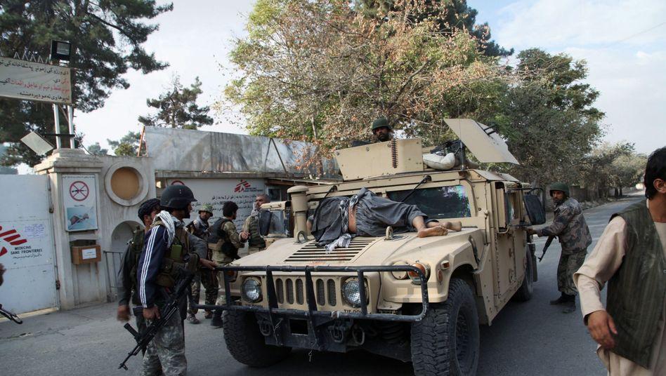 Afghanische Sicherheitskräfte nach dem Angriff: Ein Verletzter soll auf dem Fahrzeug weggebracht werden