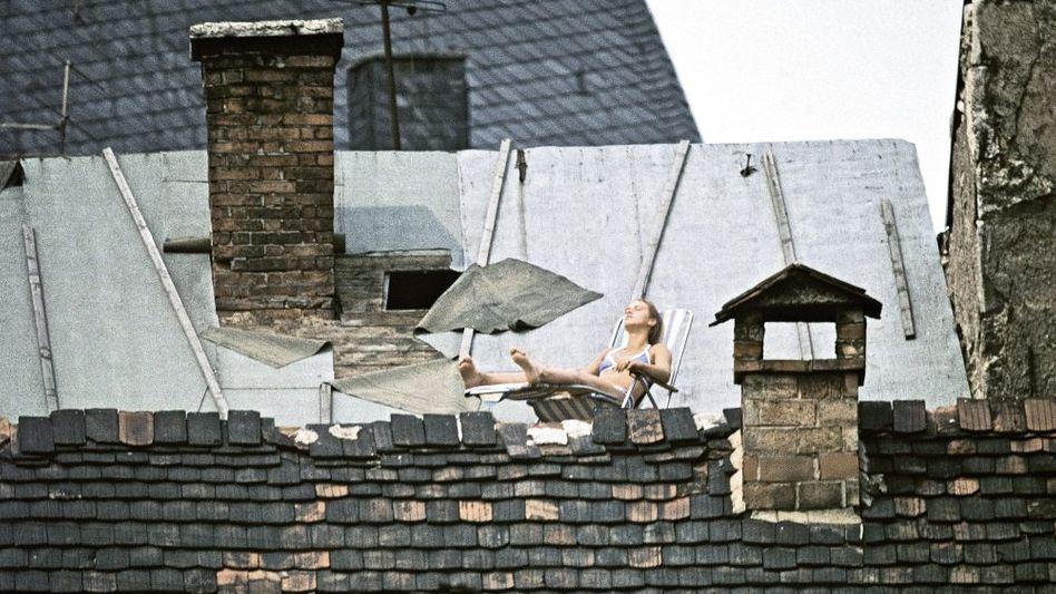 Eine junge DDR-Bürgerin sonnt sich auf ihrer selbstgebauten Dachterrasse. Besetzte Wohnungen in maroden Häusern waren Freiräume für junge Leute.