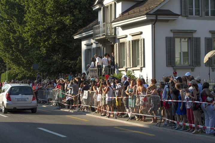 Members of the media and fans stand near Tina Turner's Villa Algonquin during her wedding celebrations in Küsnacht, Switzerland.