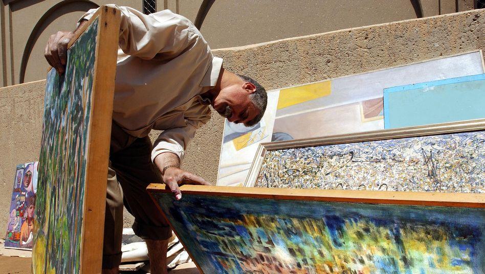 Ein irakischen Beamte inspiziert Werke aus einem Haus Saddam Husseins 2003.