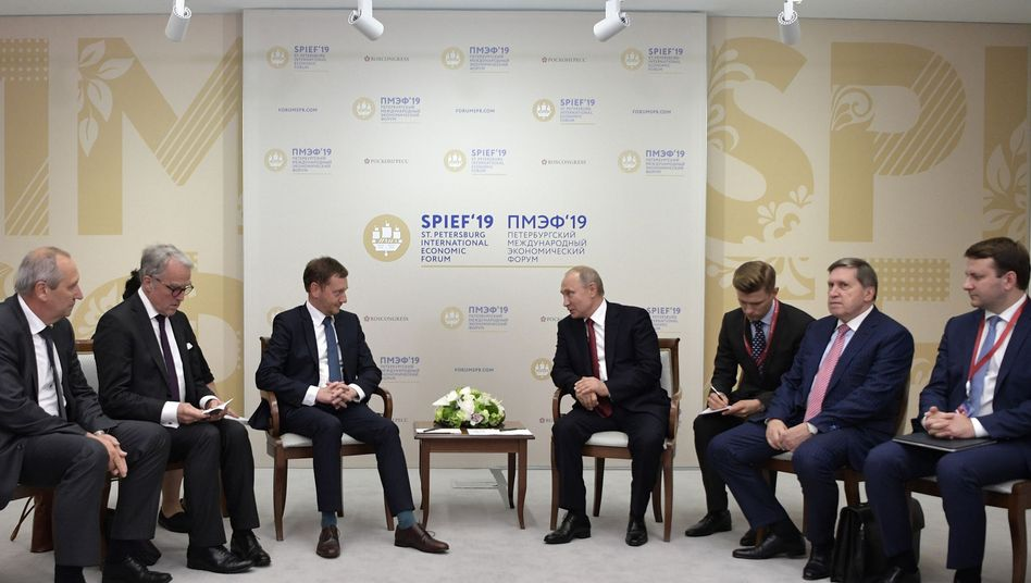 Saxony's Governor Michael Kretschmer sits together with Russian President Vladimir Putin at the Petersburg Economic Forum.