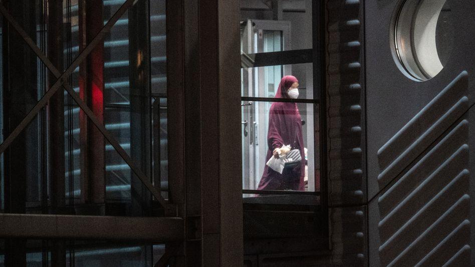 Eine verschleierte Frau betritt am späten Mittwochabend aus der Gangway einer Chartermaschine heraus einen abgeschirmten Bereich der Bundespolizei am Flughafen Frankfurt