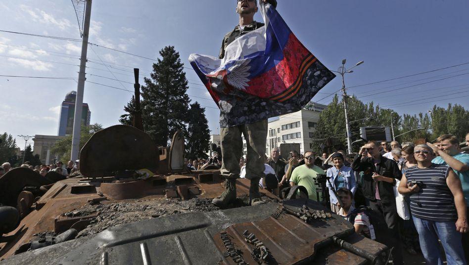 Separatist mit russischer Fahne in Donezk: Triumphgebaren auf beiden Seiten