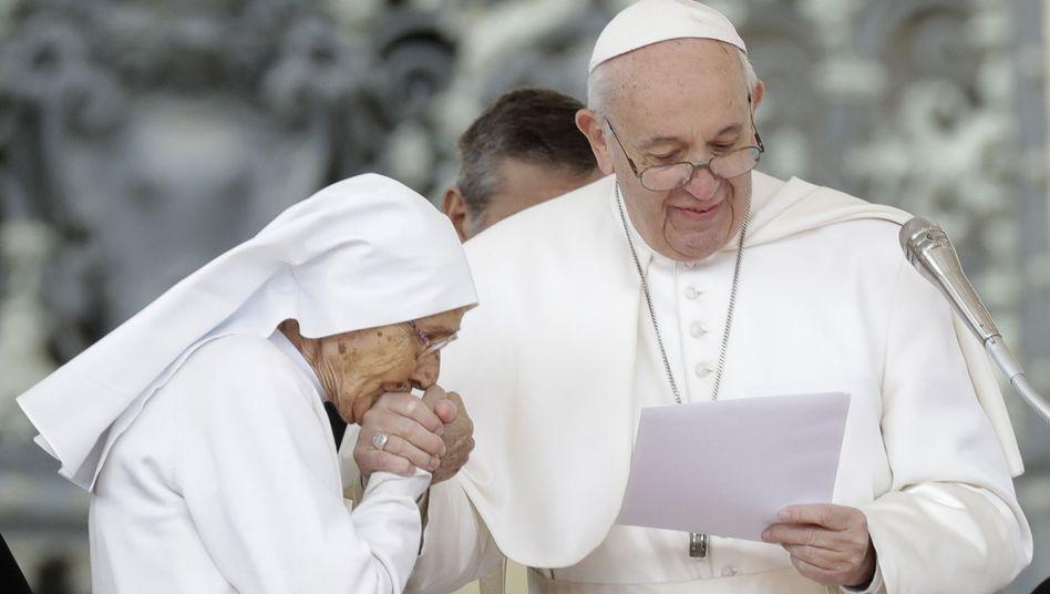 """Die 85-jährige Schwester Maria Concetta Esu küsst Papst Franziskus die Hand, während er ihr bei seiner wöchentlichen Generalaudienz auf dem Petersplatz einen """"Pro Ecclesia et Pontifice""""-Preis überreicht"""