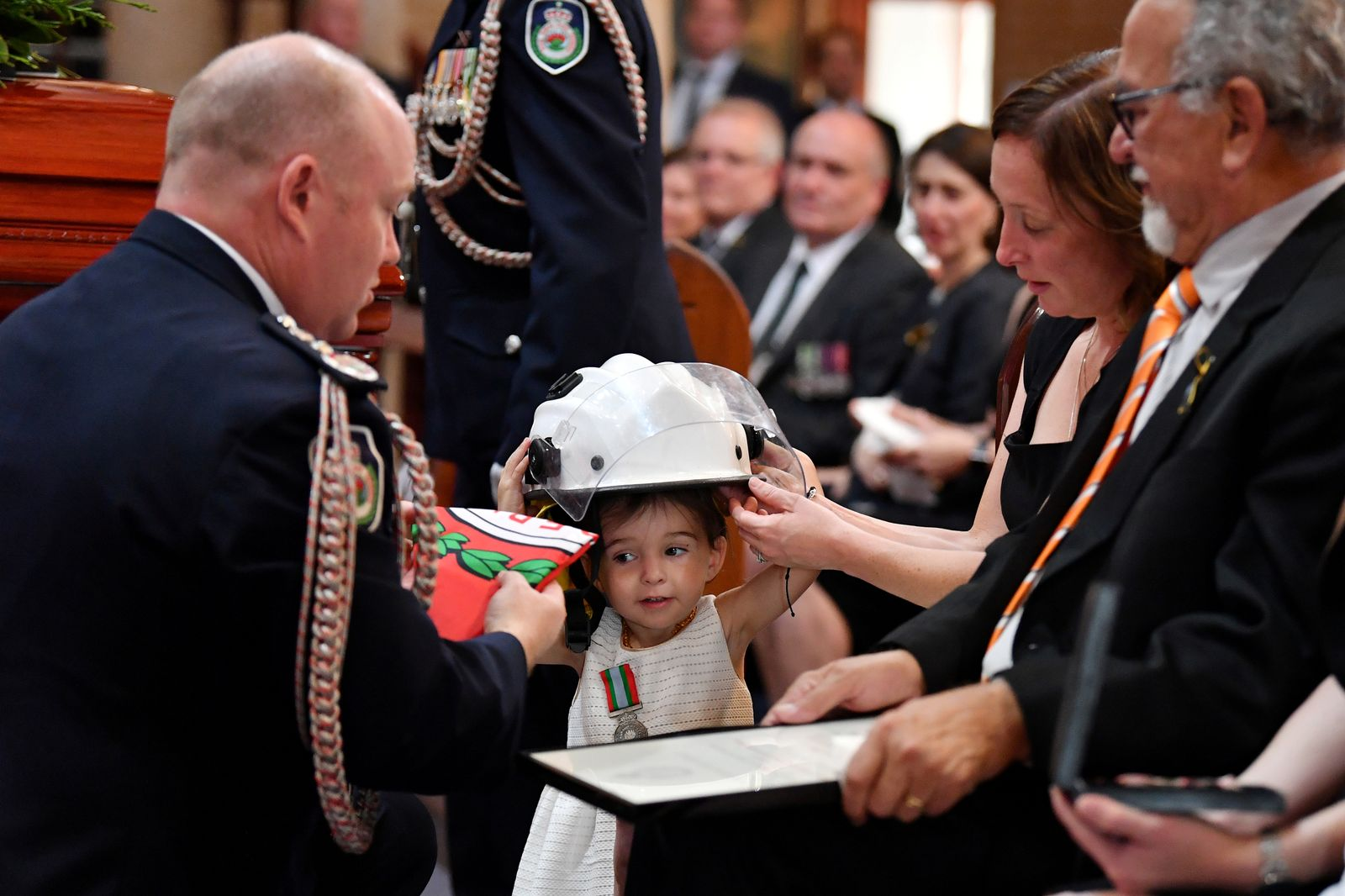 Charlotte O'Dwyer, the daughter of Rural Fire Service volunteer Andrew O'Dwyer, receives her father's helmet during the funeral for NSW RFS volunteer Andrew O'Dwyer at Our Lady of Victories Catholic Church in Horsley Park
