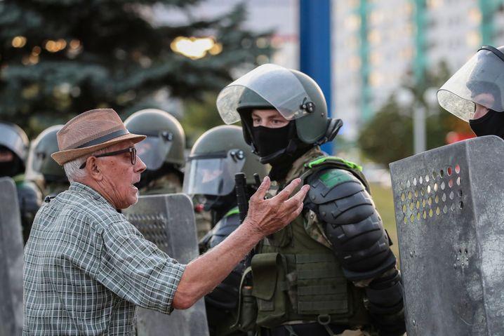 Ein Mann redet auf einen Beamten in der belarussischen Hauptstadt ein