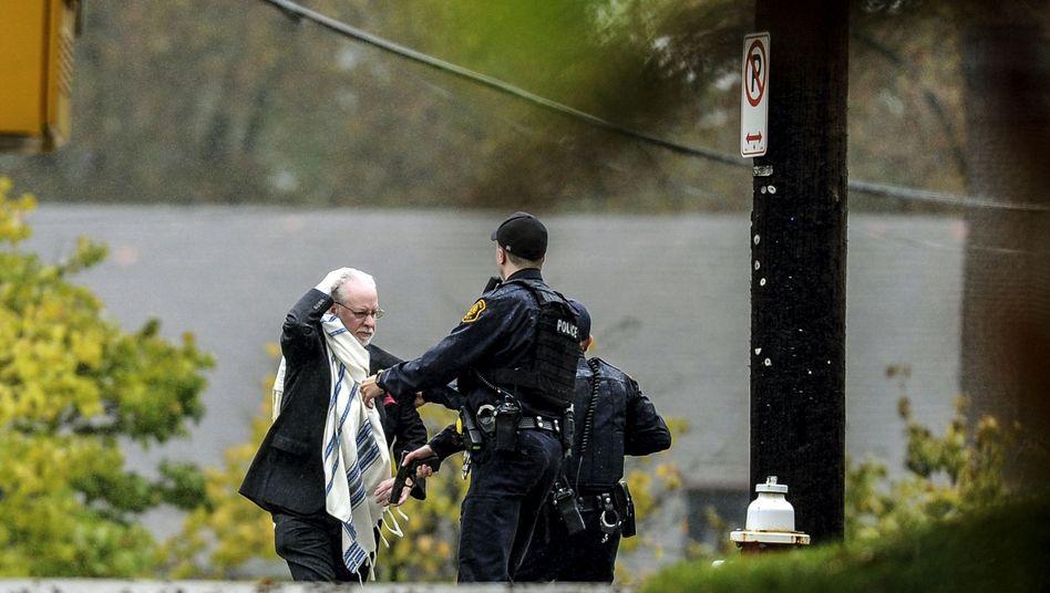 Ein geretteter Mann mit Polizei vor der Tree-of-Life-Synagoge
