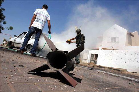 Sderot: Ein Polizist löscht ein Auto, das von einer Kassam-Rakete in Brand gesetzt worden war