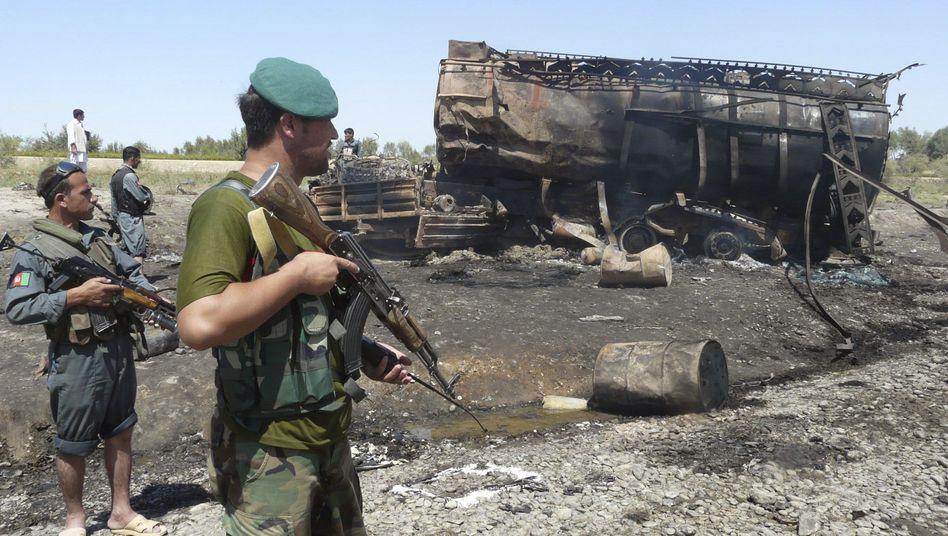 Afghanische Sicherheitsmitarbeiter neben einem ausgebrannten Tanklastzug, 4. Sept. 2009