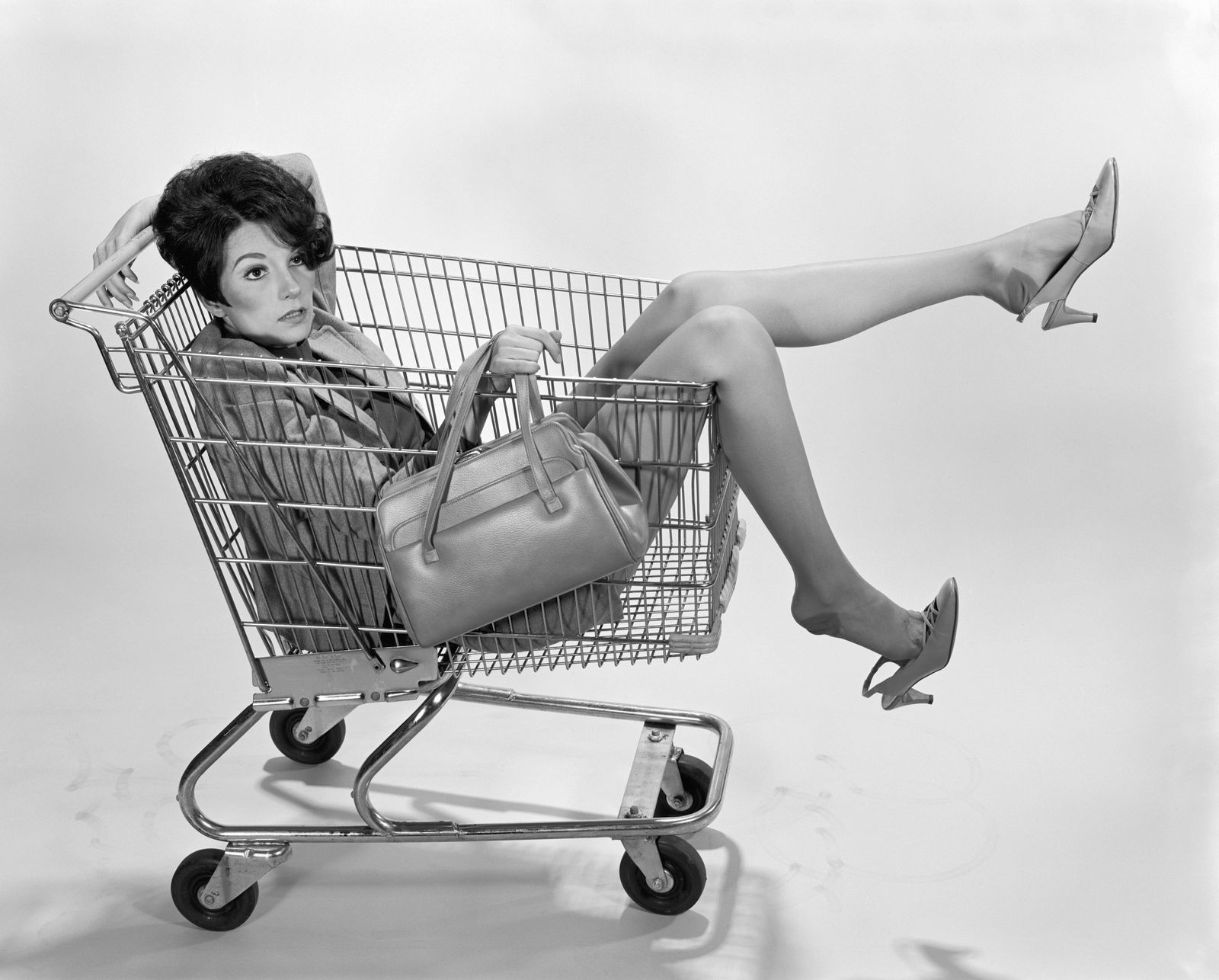 Woman sitting in shopping cart.