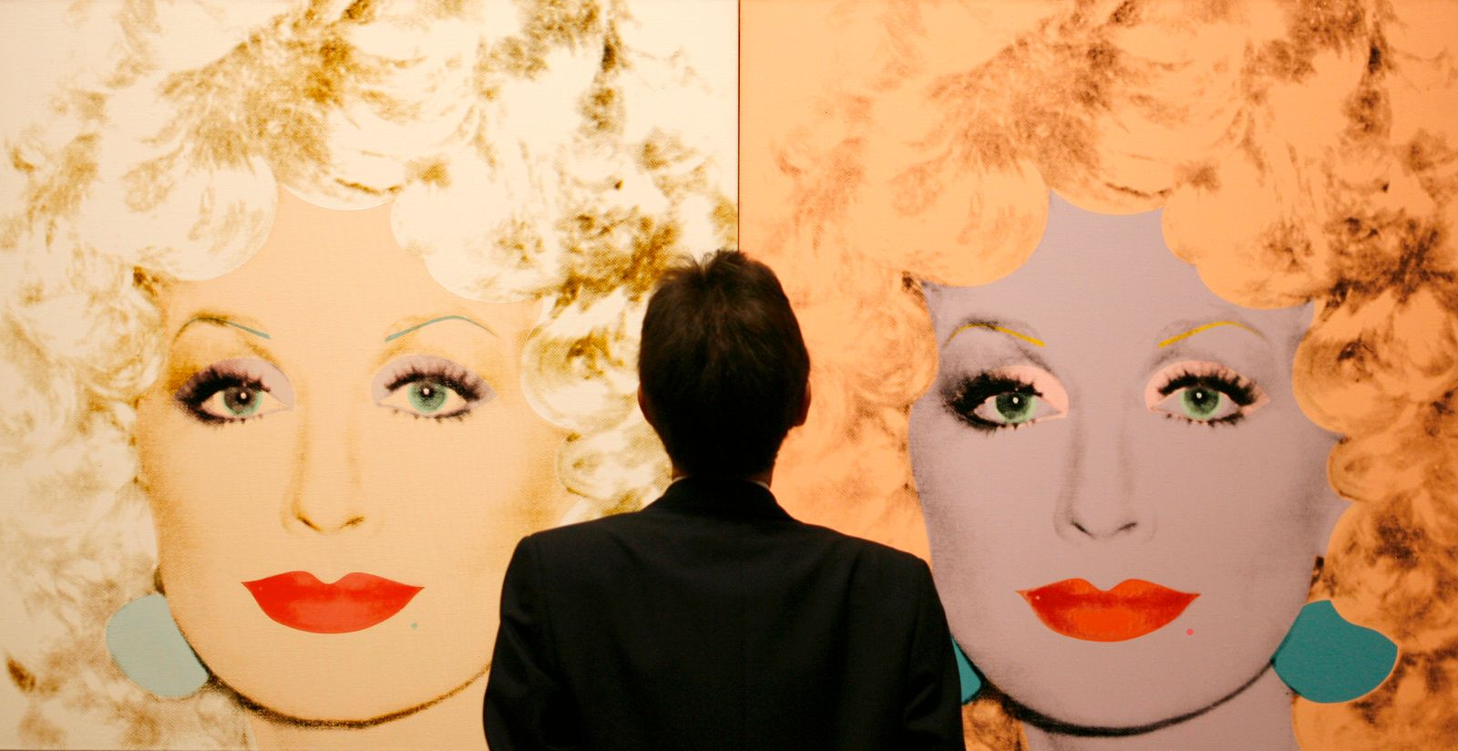 A gallery attendant stands in front of canvas prints of singer and actress Dolly Parton during the setting up of an Andy Warhol exhibtion in the National Gallery Complex in Edinburgh, Scotland