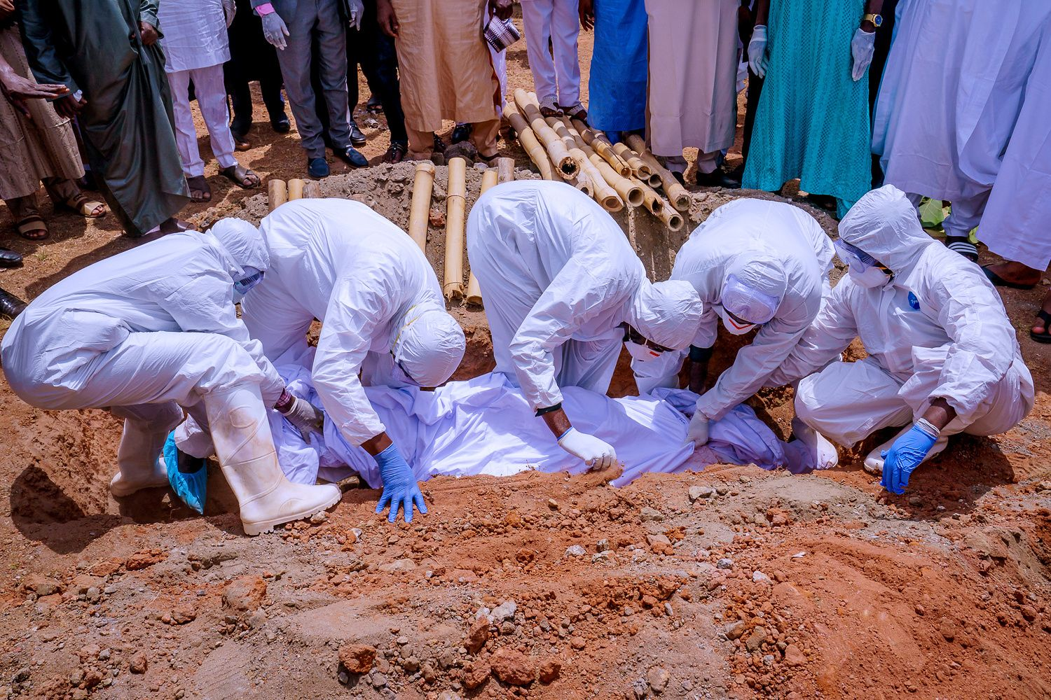 Men wearing protective gears carry the coffin of the Nigerian president's chief of staff Abba Kyari