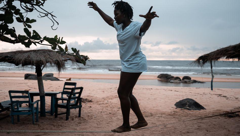 """Kadiatu Kamara am Strand von Bureh Beach in Sierra Leone: """"Surfen hat mir durch die Ebolakrise geholfen, jetzt soll es anderen Frauen durch Corona helfen"""""""