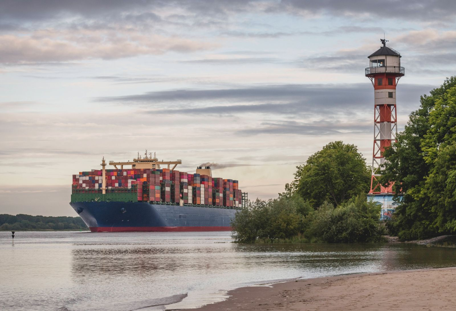 Germany, Hamburg, Container ship on Elbe river and Wittenbergen lighthouse at sunset KEBF01672
