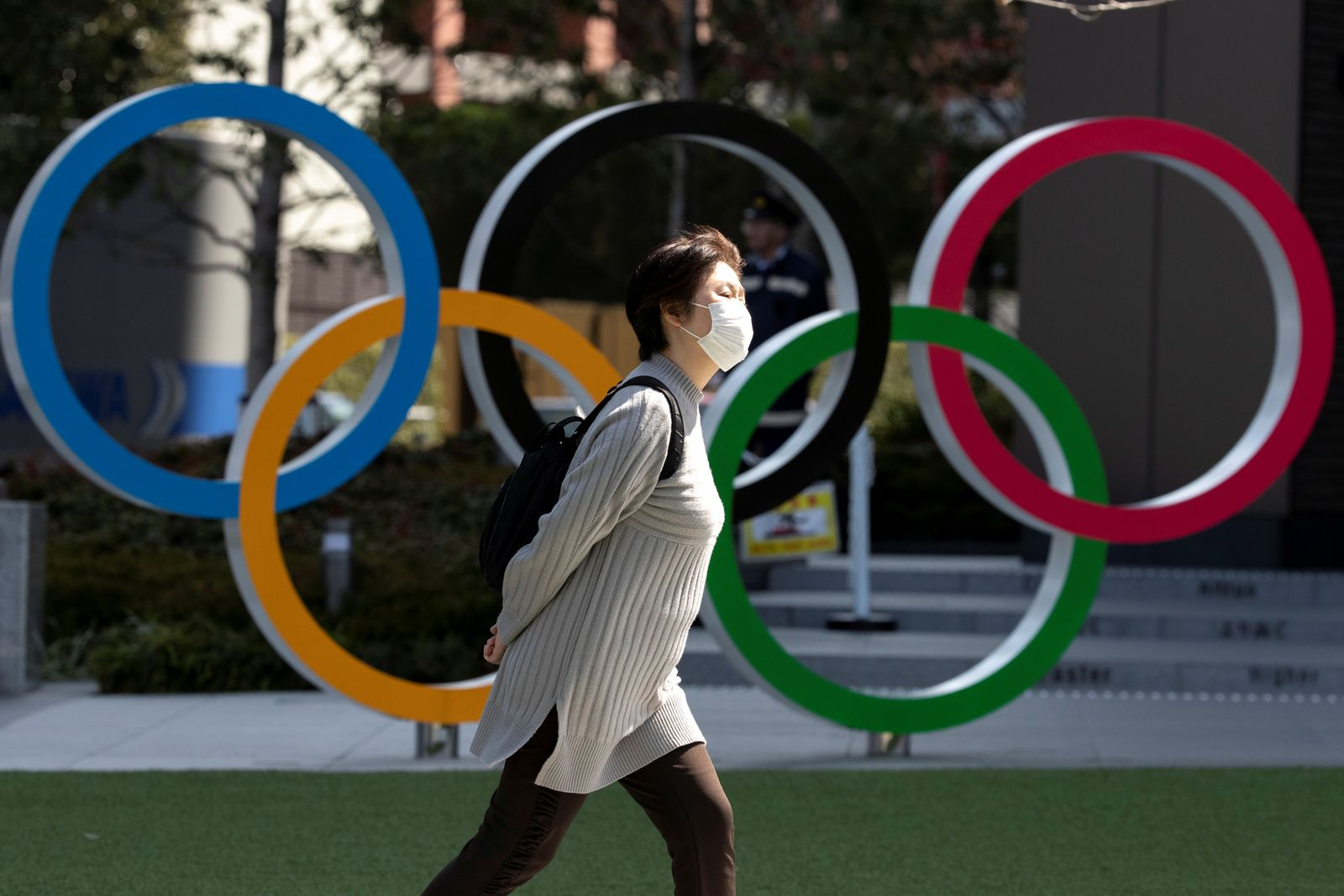 A woman wearing a protective face mask, following an outbreak of the coronavirus disease (COVID-19), walks past the Olympic rings in front of the Japan Olympics Museum in Tokyo