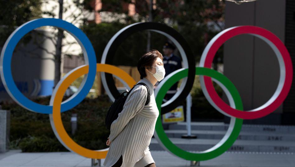 Frau mit Schutzmaske vor dem Olympia-Museum in Tokio: Die Sommerspiele werden wegen der Coronakrise verschoben
