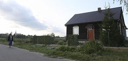 """A woman walks past the site of an alleged incest abuse case in the Eastern Polish village of Grodzisk. Prime Minister Donald Tusk has responded to the case by calling for """"chemical castration"""" for pedophiles."""