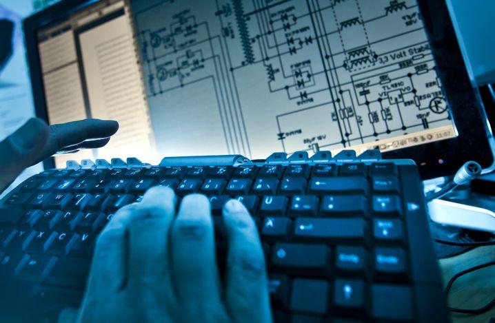 Mann tippt auf einer Computer-Tastatur vor einem elektrischen Schaltplan: Gern zum Bebildern von Hacker-Angriffen genutzt