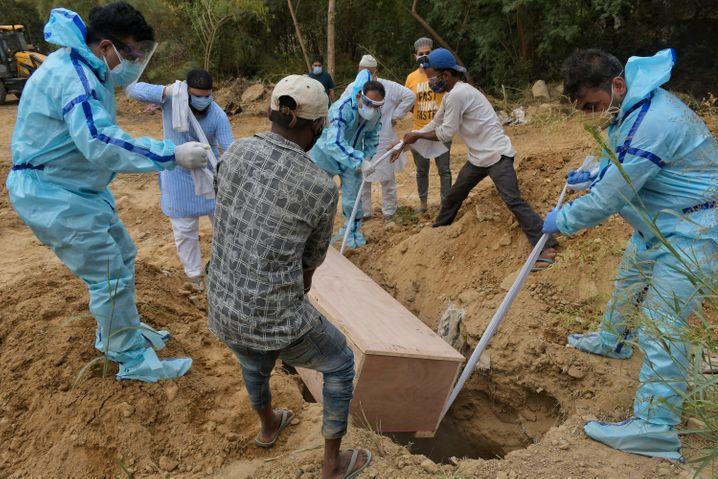 Ein Corona-Opfer wird auf einem Friedhof in Neu-Delhi beigesetzt