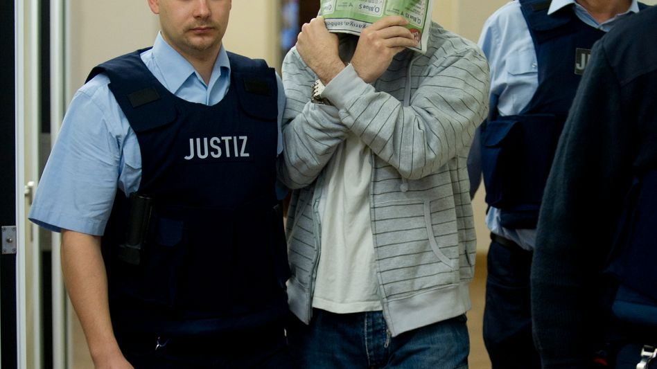 Hussam S. covered his face as he entered the Koblenz, Germany courtroom on Thursday.