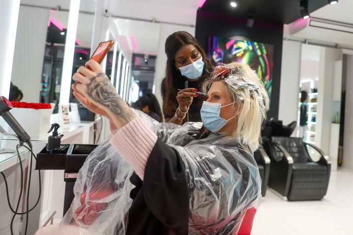 Als erster Kundin nach der Wiedereröffnung werden dieser Frau die Haare geschnitten und gefärbt