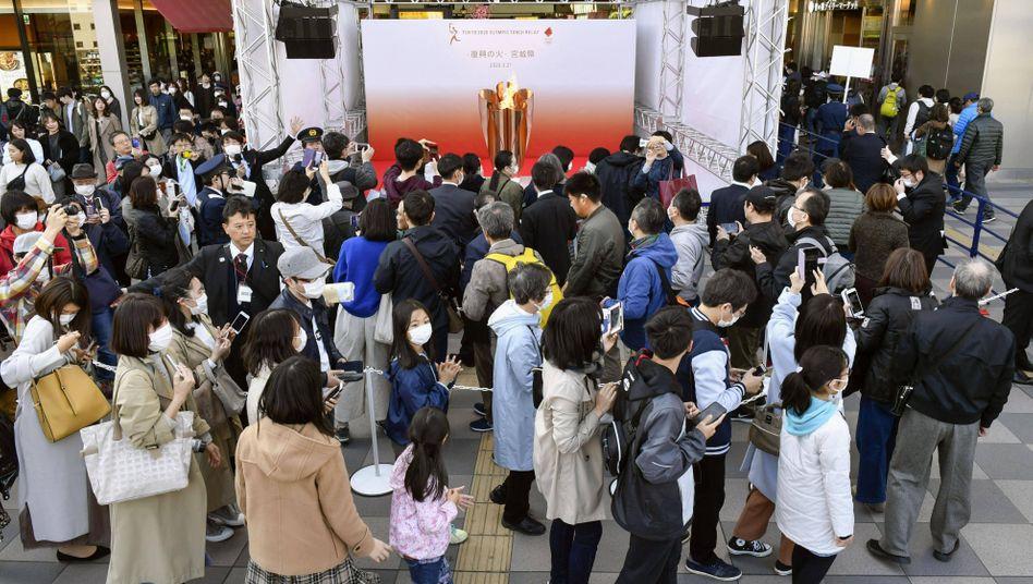 Am Bahnhof Sendai in der Präfektur Miyagi wird die olympische Flamme in einem goldenen Kessel gezeigt - und alle wollen es sehen